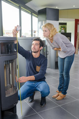 Man measuring woodburner