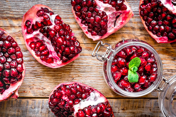 sliced pomegranate on wooden background top view