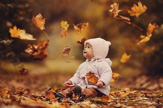 Маленький ребенок сидит в осеннем лесу и бросает желтые листья