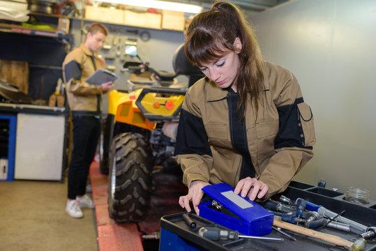 mechanic choosing tools to fix quad bike