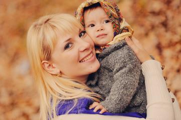 Молодая мама обнимает свою маленькую дочь в осеннем парке