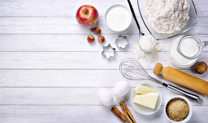 Baking ingredients: flour, eggs, milk, butter, brown sugar, cinnamon, nuts, yogurt, walnut and apple with eggbeater, cake pans and rolling pin