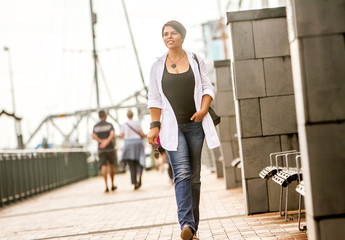 outdoor portrait of young happy smiling woman on urban city background