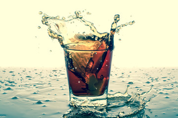 Splashing in glass with soda, ice cubes, white background. Old retro vintage style.
