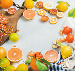Natural fresh citrus fruits slices on wooden rustic cutting board over grey marble table background, selective focus, copy space