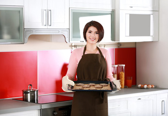 Young woman holding baking tray with  chocolate cookies on kitchen at home