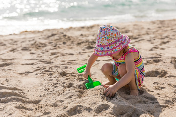 Little girl in a hat and sundress plays with a toy shovel on the beach