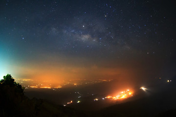 Milky way galaxy over foggy mountains at Phutabberk Phetchabun in Thailand. Long exposure photograph.with grain