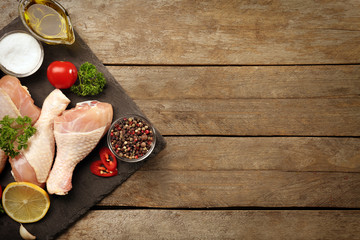Raw chicken legs with spices on wooden background