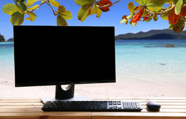 Computer monitor Business on wooden table background sea .copy space.