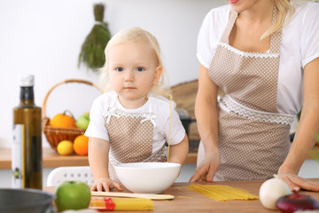 Happy family in the kitchen. Mother and child daughter  cooking tasty breakfest
