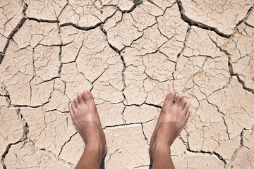 Crack dry ground on foot, drought concept.
