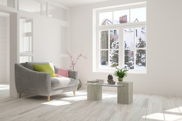 White room with armchair and winter landscape in window. Scandinavian interior design