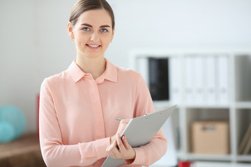 Portrait of business woman looking at the camera holding a folder in her hands and smiling