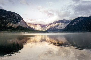 Outdoor nature of idyllic summer landscape with clear mountain lake of Hallstatt village in the Liezen District of Styria, Austria, Europe. Sunset reflection on a Hallstatter See lake in the Alps