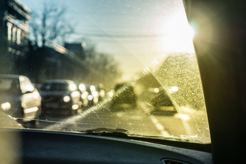 Car glass with unclean texture. Blurred road on background. Morning sunlight.