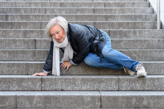 Senior woman falling down stone steps outdoors