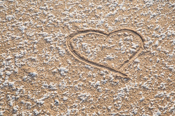 Love heart drawn on the little bit snow covered frozen sand at the seashore. Sunny, but cold winter day. Background.