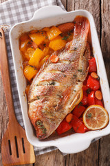 Tilapia baked with vegetables and thyme close up in baking dish. vertical top view
