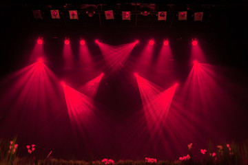 The red light from the spotlights through the smoke at the theater during the performance. Lighting equipment.