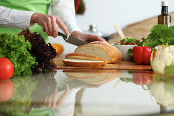 Closeup of human hands slicing bread in kitchen on the glass table with reflection. Healthy meal and vegetarian concept