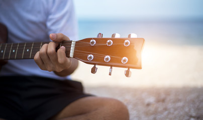 Close up handsome man playing classic guitar sitting on the beach in vacations.