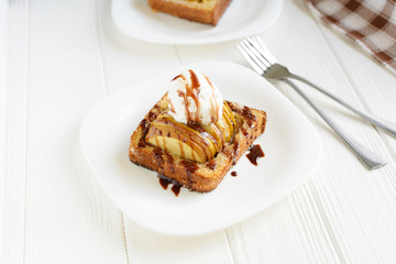 Delicious homemade dessert. Baked toast with apples and ice cream drizzled with chocolate