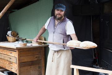 Fototapete - baker  posing with shovel and grain dough