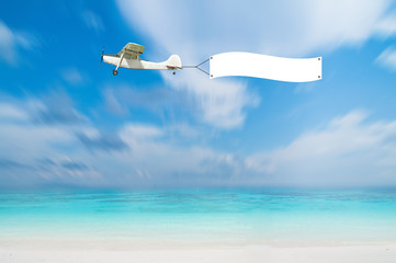 Antique Airplane with advertise board banner fly on blue sea view with blue sky, Thailand.