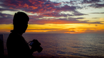 Photographer Gazing Into Sunset Over the Sea