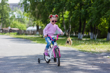 Little girl on a bicycle in summer park outdoors