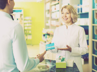 Helpful pharmacist serving and consulting man