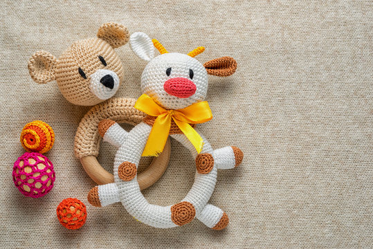 knitted rattles for toddlers and copy space. perfect background for childhood theme. cow and bear toys.