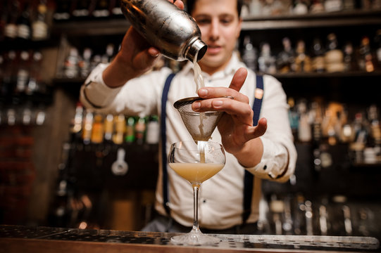 bartender pouring coctail into the glass