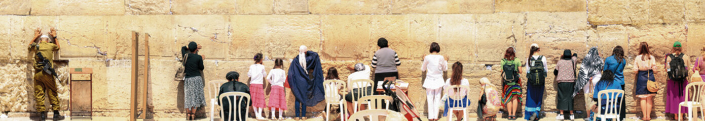 Israeli Soldier, Women And Children Praying At The Kotel, Jerusalem. The most holy place of the jewish people where everyone can come to pray.