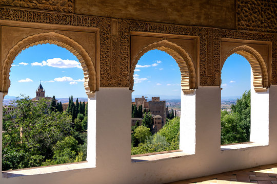 Stone arches in the world-famous Alhambra in Granada with beautiful views of the fortress and Granada.