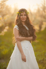 Portrait of the bride in ivory wedding dress with long curly hair walking in gardens with blossom trees like in fairy tale