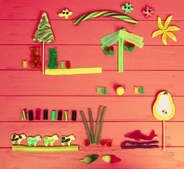 Cheerful picture of tasty jelly candies in the shape of bears, cows and trees on wooden red table