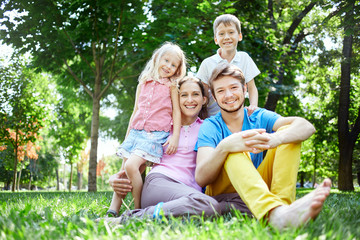 young happy family at noon in the park on the grass. Two young parents and children, boy and girl, sits on the grass and smiling looking at the camera.