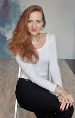 Красивая рыжеволосая девушка в белой кофте