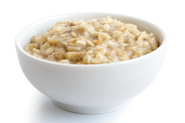Cooked whole porridge oats in white ceramic bowl isolated on white.