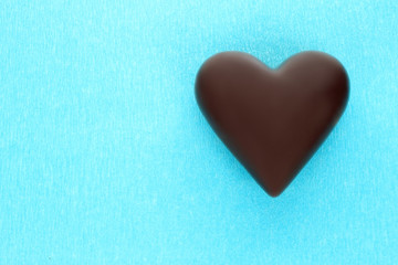 Black chocolate heart on blue background