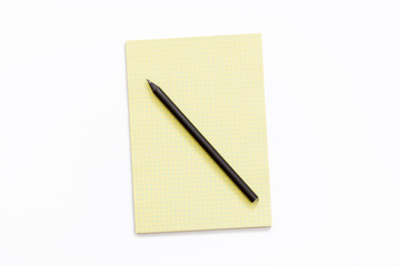 yellow Notepad and pencil on white background.