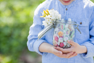 child holding a jar full of sweets