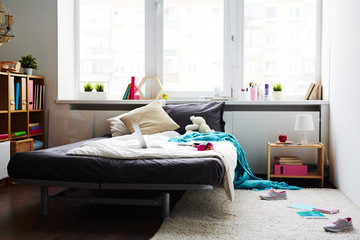 Modern messy girl bedroom with large bed, laptop, teddy bear and scattered sneakers on white soft carpet