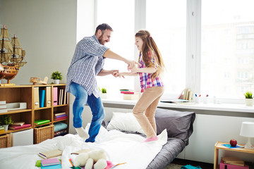 Cheerful dad and his pretty little daughter holding hands and jumping on bed covered with textbooks and notebooks, full-length portrait