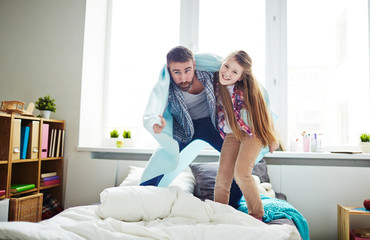 Full-length portrait of pretty little girl hugging her dad and looking at camera while standing on bed against panoramic window