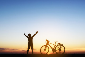 Silhouette of a biker  on the hill with sunset background, enjoying freedom and active lifestyle, having fun on a bikers tour