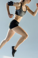 side view of running sporty woman on grey