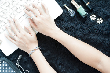 Beautiful woman's hands shopping online on white laptop with her beauty items on black
